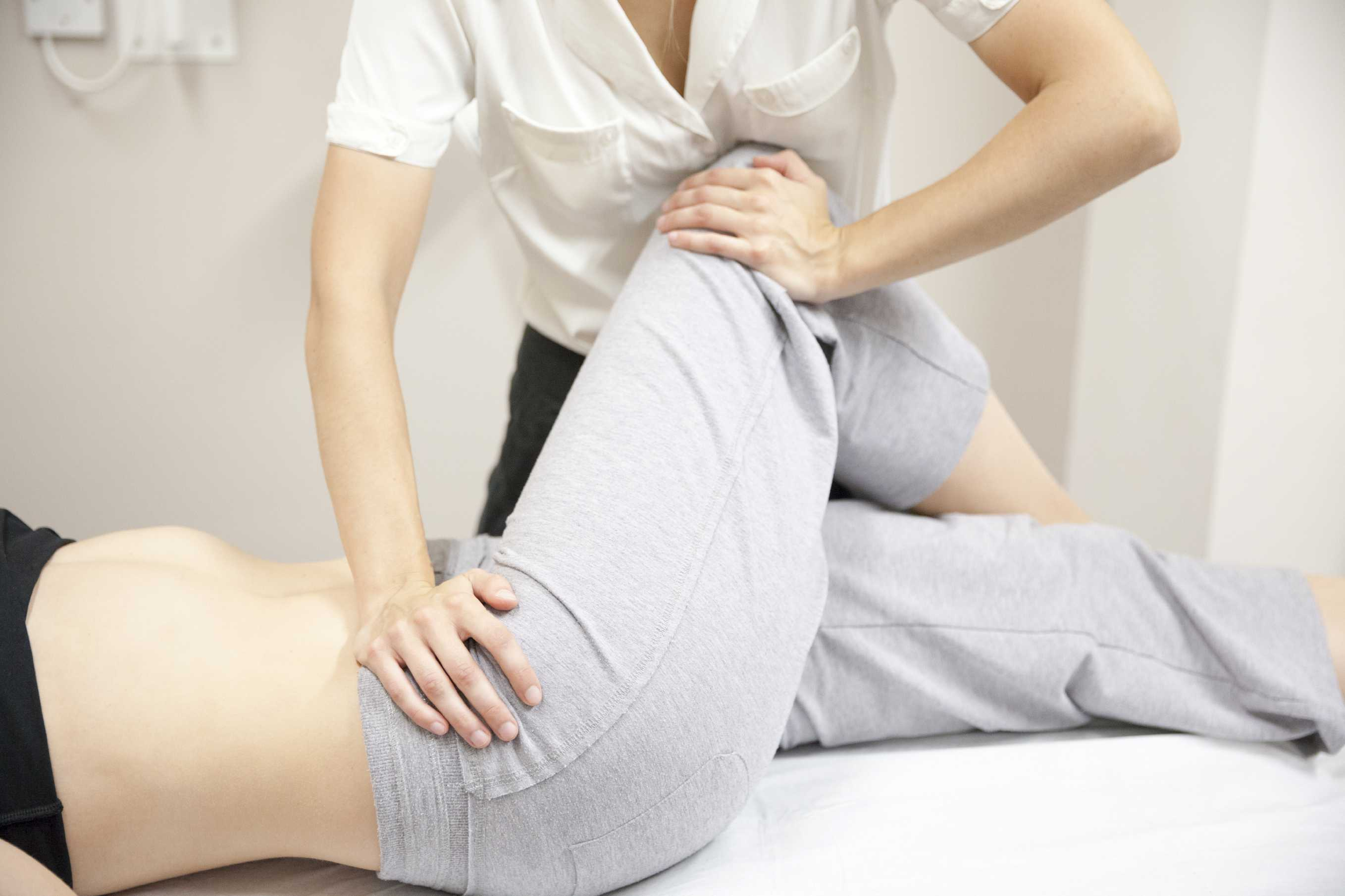 Woman having physio done on her leg/hip